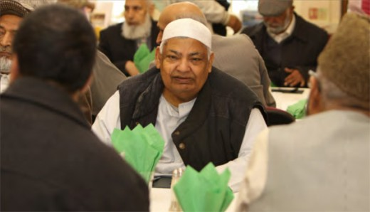 Elderly Asian man seated at communal dining table