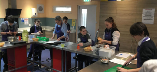 Group of young people cooking in a community kitchen